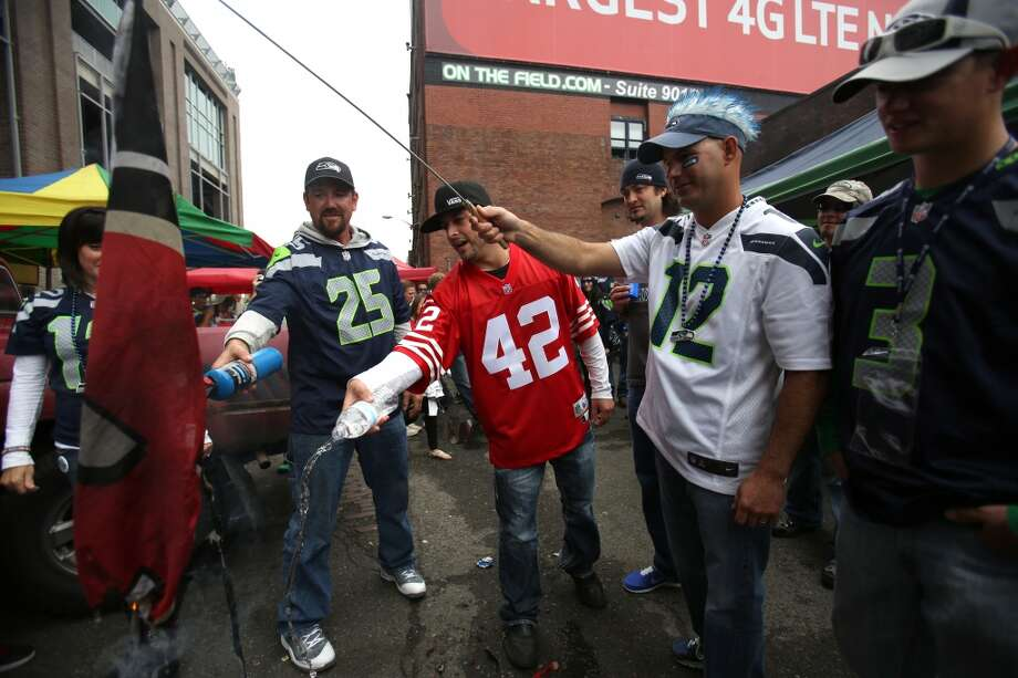 Seattle Seahawks fans try to burn a San Francisco 49ers flag as a 49ers fan steps in and douses the small fire with water outside the stadium. Photo: JOSHUA TRUJILLO, SEATTLEPI.COM