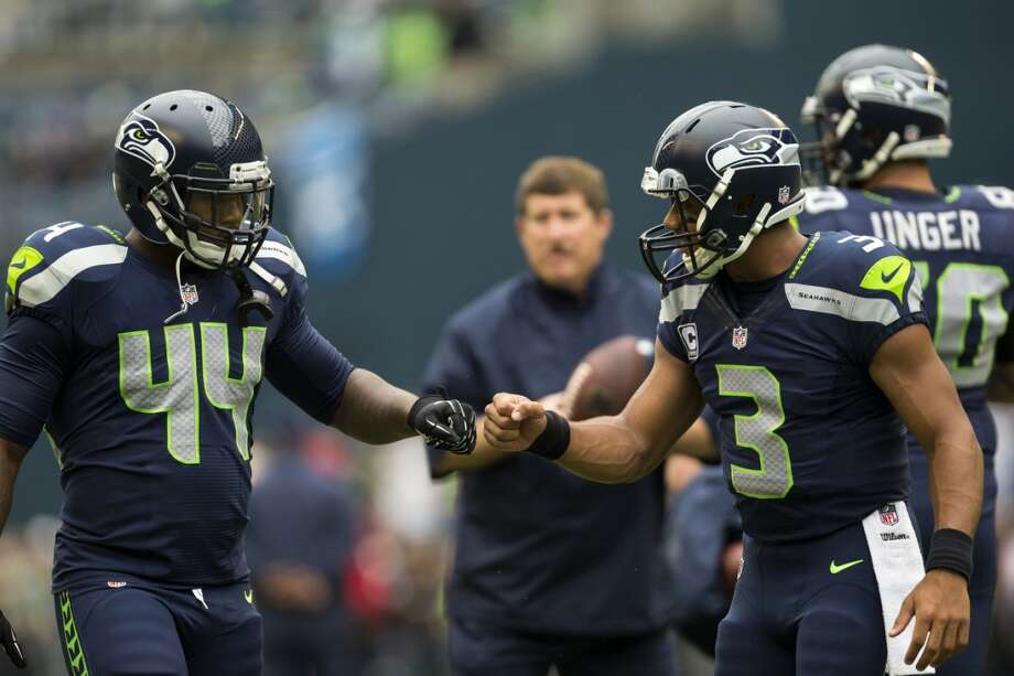 Seahawks quarterback Russell Wilson, right, bumps fists with Spencer Ware, left, while warming up. Photo: JORDAN STEAD, SEATTLEPI.COM