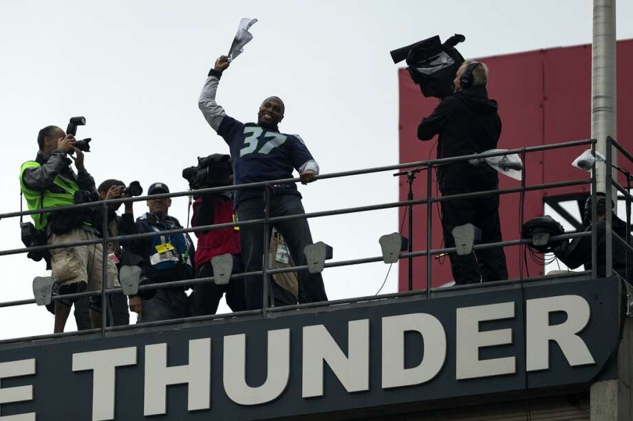 Former Seahawks running back Shaun Alexander, center, raises the 12th Man flag. Photo: JORDAN STEAD, SEATTLEPI.COM