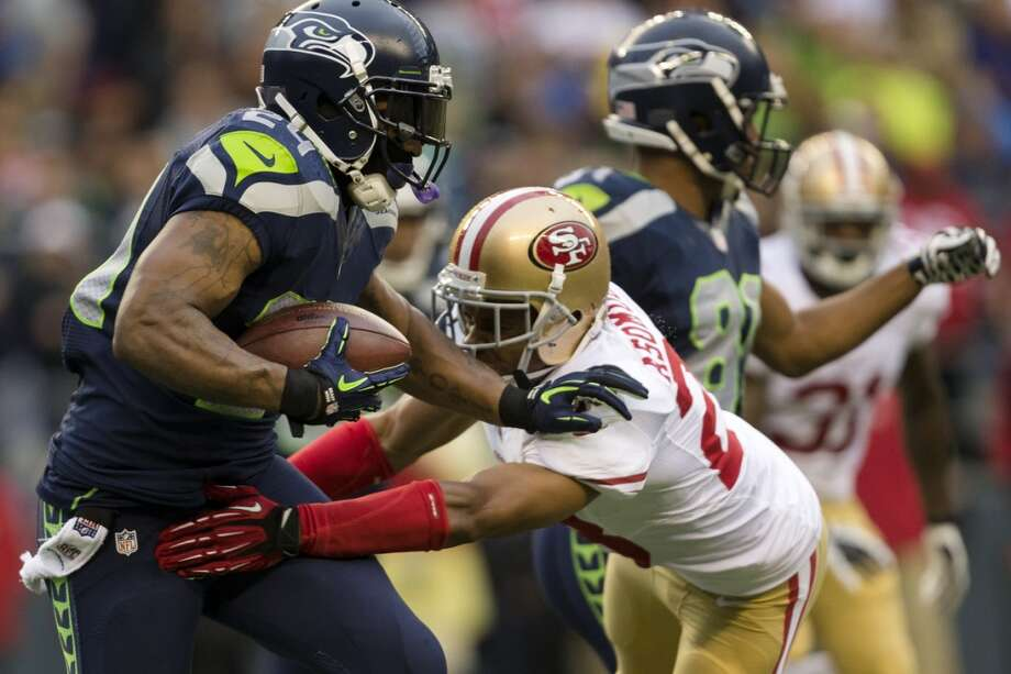 Marshawn Lynch, left, makes a run to score the first touchdown of the game against the 49ers during the first quarter of the home opener of the season at CenturyLink Field in Seattle. Photo: JORDAN STEAD, SEATTLEPI.COM