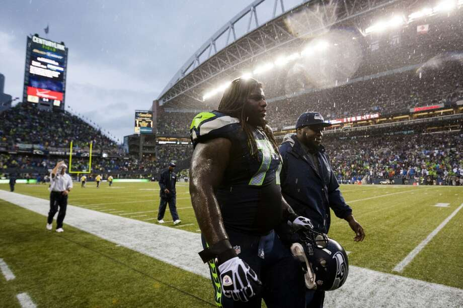 James Carpenter, center, and teammates leave the field on a rain delay. Photo: JORDAN STEAD, SEATTLEPI.COM