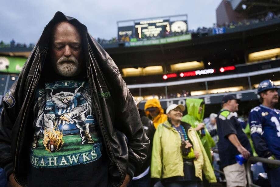 Bill Waddell, left, of Shoreline, WA, pulls his jacket over his head in a sudden heavy rain. Photo: JORDAN STEAD, SEATTLEPI.COM