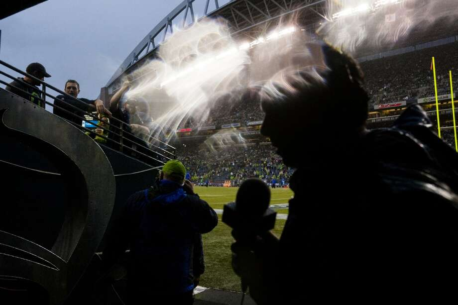 Sportscasters and media huddle beneath the tunnel in a sudden heavy rain during the first quarter. Photo: JORDAN STEAD, SEATTLEPI.COM