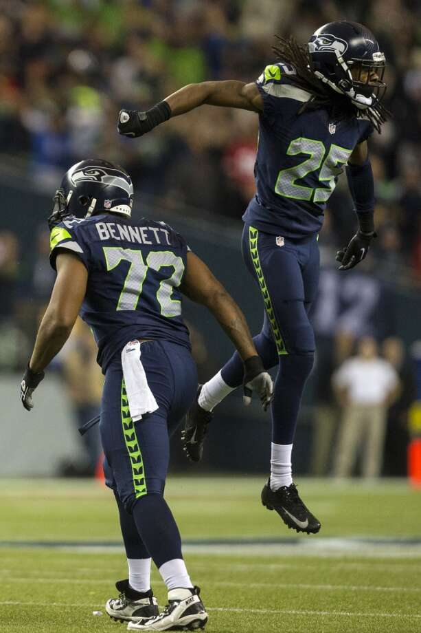 Seahawks Richard Sherman, right, and Michael Bennett, left, react to a play in the Seahawks' favor during the first half. Photo: JORDAN STEAD, SEATTLEPI.COM