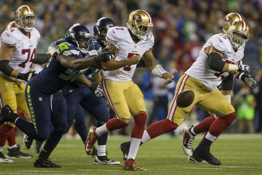 Cliff Avril, left, sacks 49ers' quarterback Colin Kaepernick, center, during the first half of the home opener. Photo: JORDAN STEAD, SEATTLEPI.COM