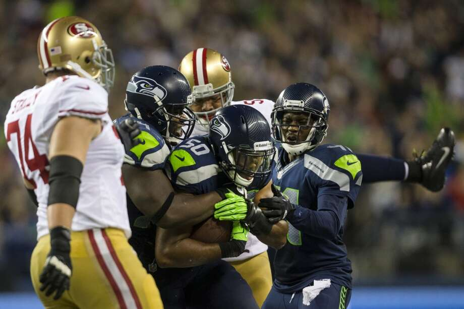 Cliff Avril, center, is hugged by teammates after sacking 49ers' quarterback Colin Kaepernick during the first half. Photo: JORDAN STEAD, SEATTLEPI.COM