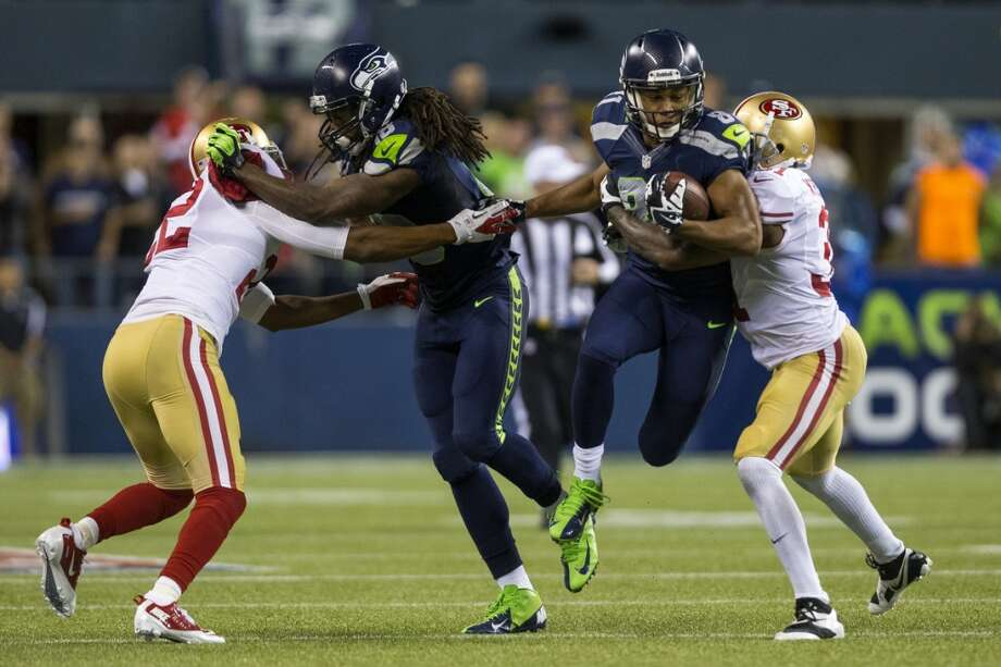 Golden Tate, center right, leaps through 49ers offense and a blocking teammate during the second half. Photo: JORDAN STEAD, SEATTLEPI.COM