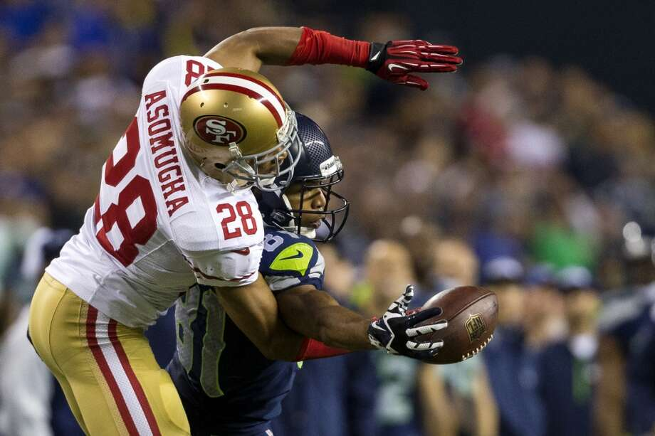 Backed by Nnamdi Asomugha, left, Seahawk Golden Tate, center, intercepts a pass during the second half. Photo: JORDAN STEAD, SEATTLEPI.COM