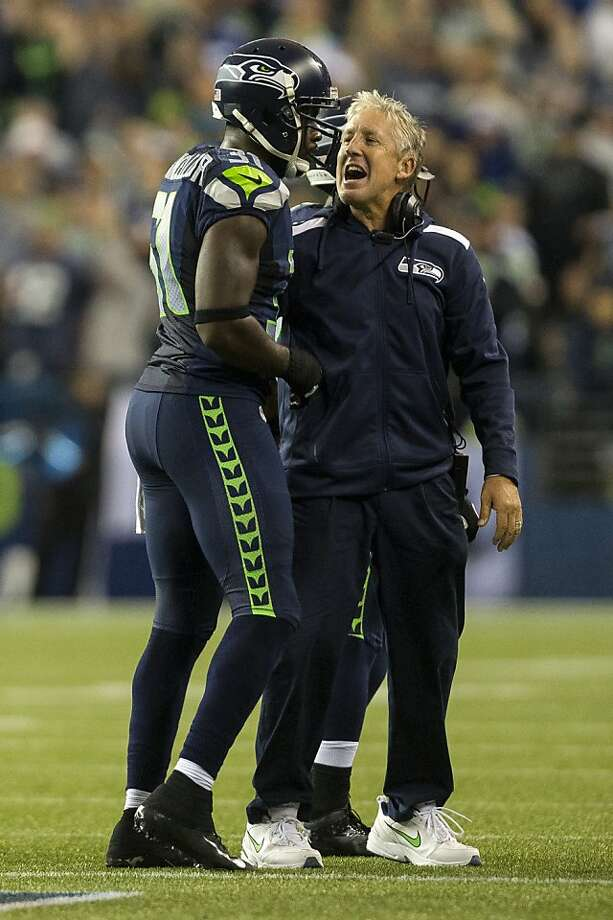 Head coach Pete Carroll, right, welcomes players to the sideline following a play in the Seahawks' favor during the first half of the home opener Sunday, September 15, 2013, at CenturyLink Field in Seattle. The Seahawks led the 49ers 5-0 at the half. (Jordan Stead, seattlepi.com) Photo: Jordan Stead, SEATTLEPI.COM