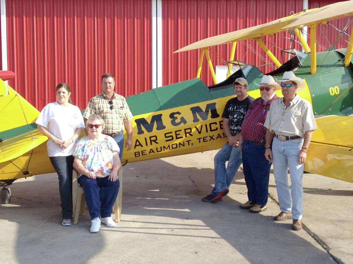 The Mitchell family stands in front of one of the first planes that launched their business. The Stearman biplane was among the first to plant rice by air in Texas. M&M Air Service from left to right: Lisa, Gail, Mark, Andy, George and David Mitchell.