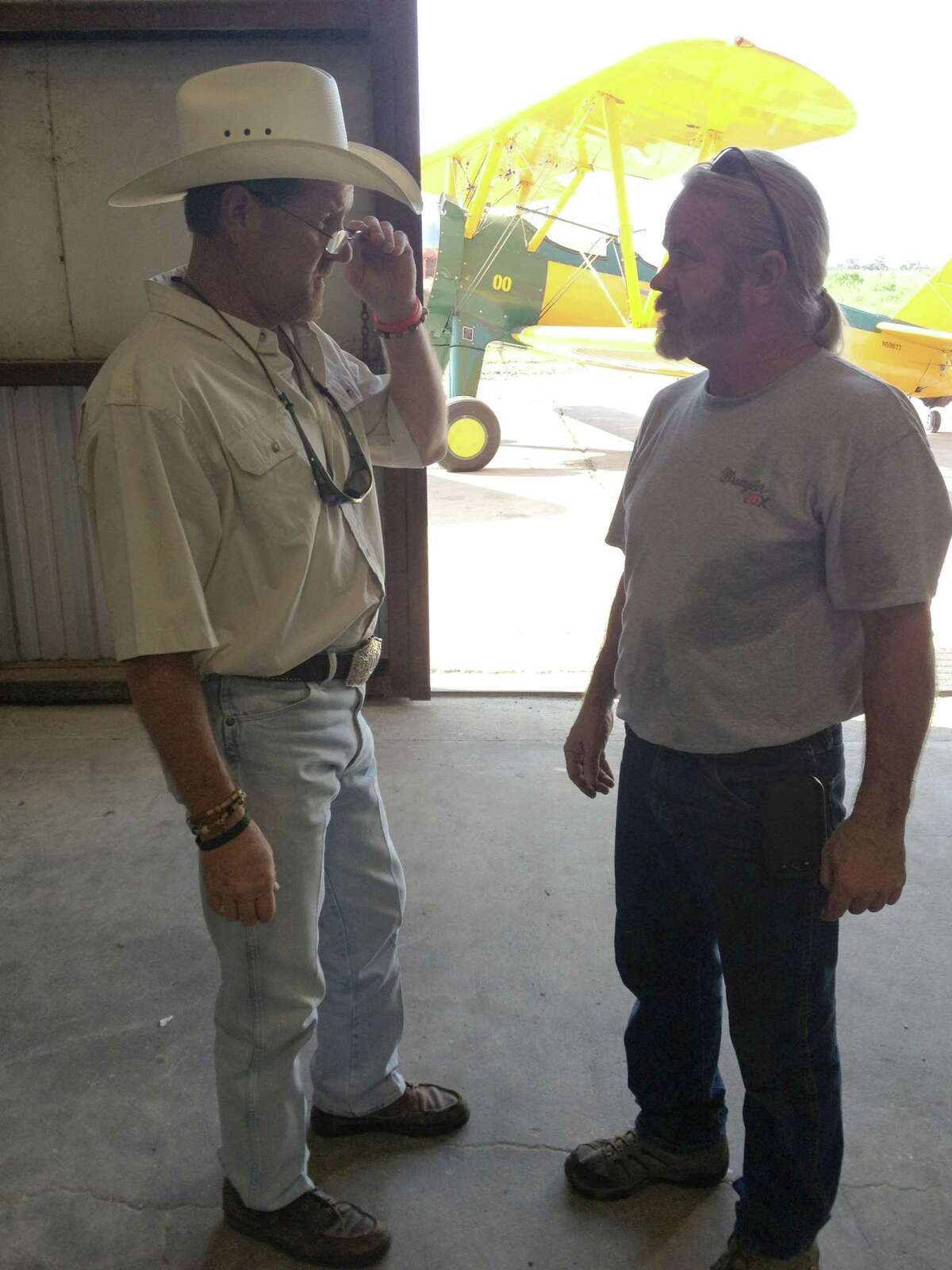 David Mitchell, left, talks with mechanic Brad CAlloway about a new distribution system being installed in their planes. In the background is a Stearman plane, one of the first planes used by the company to seed Southeast Texas' rice fields by air.