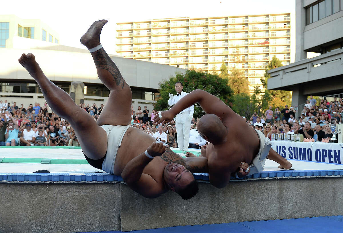 Siosifa Isamau of Tonga is tosssed out of the ring by Byambajav Ulambayar of Mongolia during the Men's Heavyweight of the 13th US Sumo Open at the Japanese American Cultural & Community Center Plaza on September 15, 2013 in Los Angeles, California.