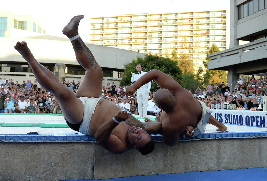 Siosifa Isamau of Tonga is tosssed out of the ring by Byambajav Ulambayar of Mongolia during the Men's Heavyweight of the 13th US Sumo Open at the Japanese American Cultural & Community Center Plaza on September 15, 2013 in Los Angeles, California. Photo: Harry How, Getty Images / 2013 Getty Images