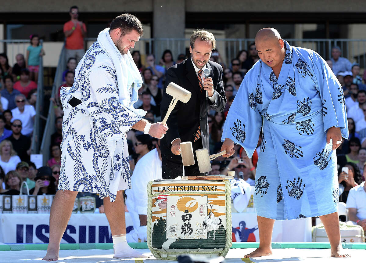 Soslan Gagloev of Russia, Director US Sumo Open Andrew Freund, and Byambajav Ulambayar of Mongolia break open a ceremonial barrell of sake before the start of the13th US Sumo Open at the Japanese American Cultural & Community Center Plaza on September 15, 2013 in Los Angeles, California.