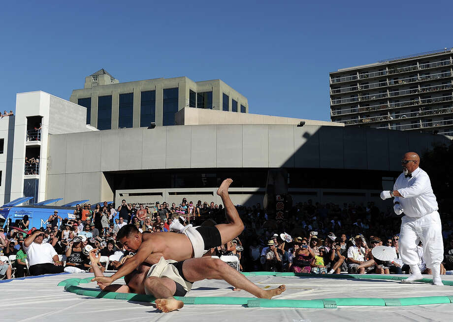 Tumenjargal Avirmed of Mongolia pushes out Christopher Sinnott to win the match in the Men's Lightweight during the 13th US Sumo Open at the Japanese American Cultural & Community Center Plaza on September 15, 2013 in Los Angeles, California. Photo: Harry How, Getty Images / 2013 Getty Images