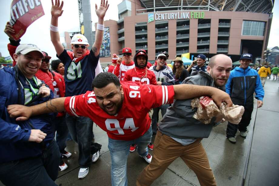 A San Francisco 49ers fan playfully pushes aside Seattle Seahawks fans in the North Lot before the game. Photo: JOSHUA TRUJILLO, SEATTLEPI.COM