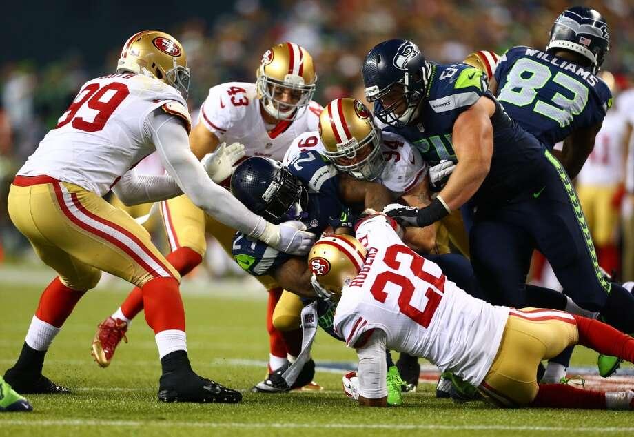San Francisco 49ers players work to bring down Seattle Seahawks Marshawn Lynch as Lynch gains yardage. Photo: JOSHUA TRUJILLO, SEATTLEPI.COM