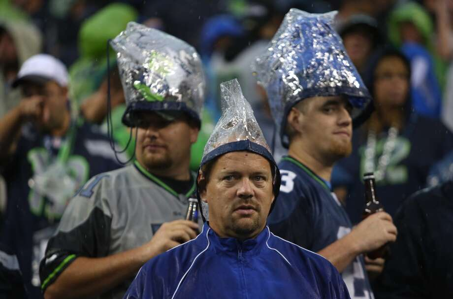 Seattle Seahawks fans use plastic bags to cover their heads during the weather delay of the game against the San Francisco 49ers. Photo: JOSHUA TRUJILLO, SEATTLEPI.COM