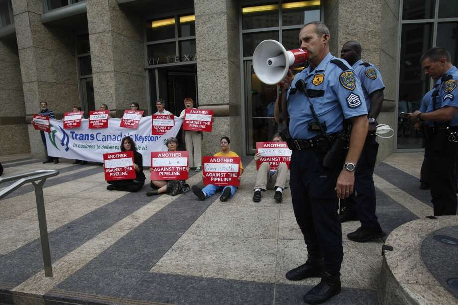 Protestors perform civil disobedience by chanting and holding signs while criminally trespassing Sept. 16, 2013 in Houston in front of the TransCanada office in downtown.