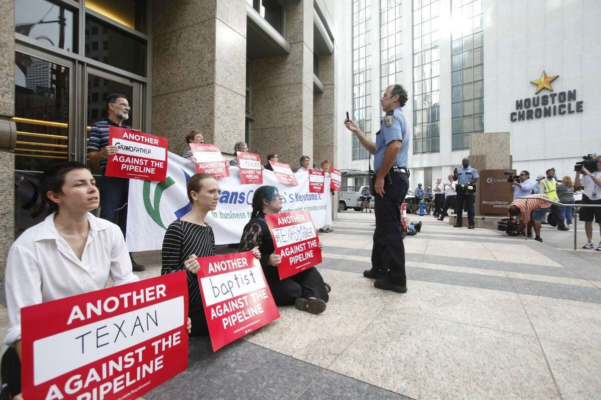 Pipeline protestors chant and hold signs in downtown Houston on Sept. 16, 2013.