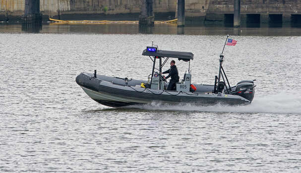 "A DC Police patrol boat speeds down the Anocostia River next to the US Navy yard September 16, 2013 in Washington, DC. At least one unidentified gunman opened fire at the US Navy Yard in Washington on Monday and was at large after killing ""multiple"" victims and wounding several more, officials said. Police and FBI agents descended on the area in force as helicopters swarmed overhead, amid reports a shooter was armed with an assault rifle and was holed up at the complex. ""We believe there were multiple deaths,"" a US defense official, speaking on condition of anonymity, told AFP. The precise death toll remained unclear, the official said. A Washington DC police officer and another law enforcement officer had been shot while the gunman had allegedly barricaded himself in a room in a headquarters building, media reported. Photo: PAUL J. RICHARDS, AFP/Getty Images / 2013 AFP"