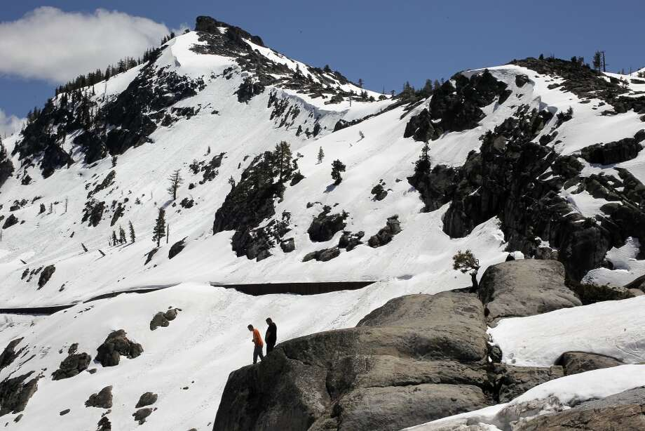Visitors to a lookout along old US highway 40 look out over snow capped Donner Peak in a June 2011 file photo. Snow depth monitoring in nearby Soda Springs shows that is is the deepest snow at this date in the high elevations since records were begun in 1868 by the folks that built the Transcontinental Railroad. Photo: Michael Macor, The Chronicle