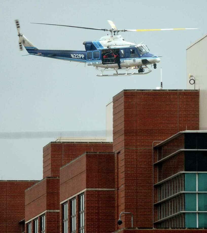 A U.S. Park Police helicopter flies over a building at the Washington Navy Yard in Washington, Monday, Sept. 16, 2013. At least one gunman opened fire inside a building at the Washington Navy Yard on Monday morning, Photo: Susan Walsh