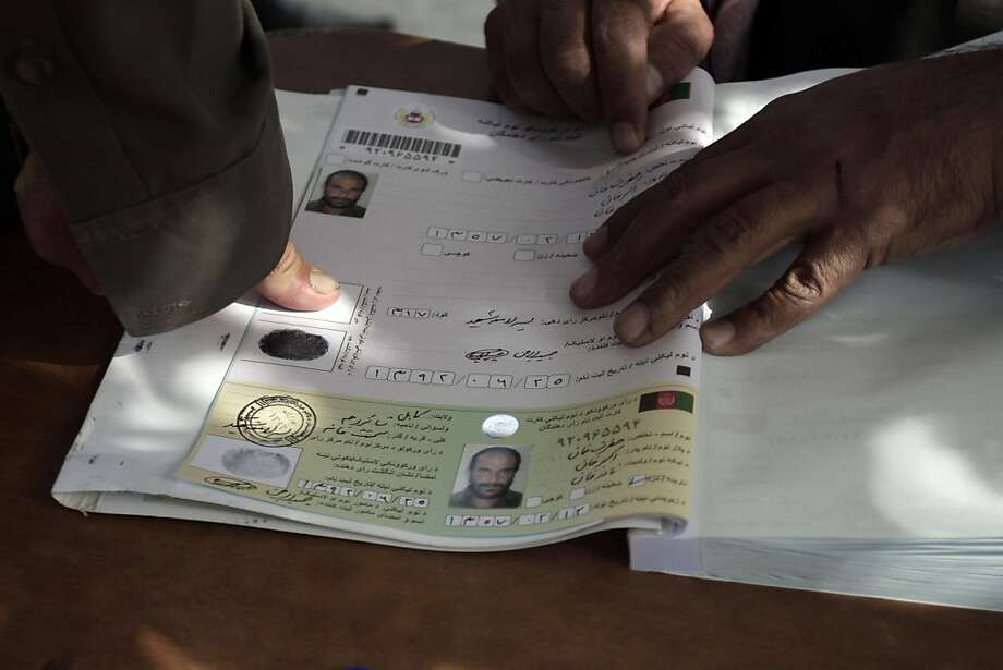 An Afghan man marks his voter registration application with his fingerprint at a Kabul center. Photo: Rahmat Gul, Associated Press