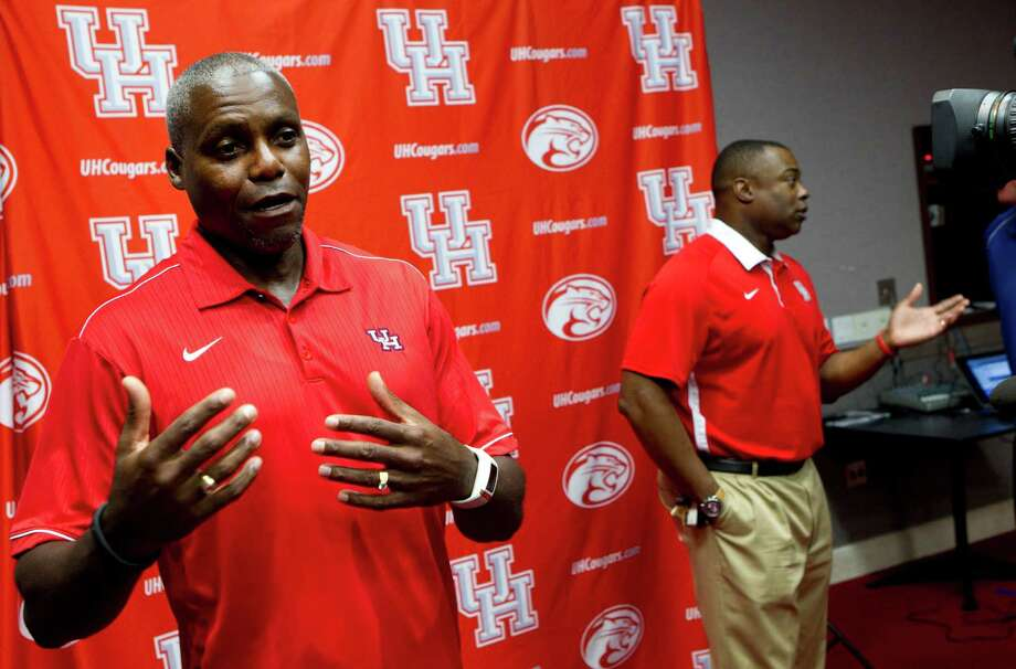 Former University of Houston track star Carl Lewis, left, and UH track coach LeRoy Burrell, right, answer questions during a news conference, as the former Olympian is introduced as a volunteer assistant coach for the UH track team Monday, Sept. 16, 2013, in Houston. Photo: Brett Coomer, Houston Chronicle / © 2013 Houston Chronicle