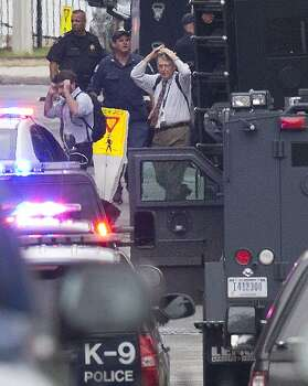 People hold their hands to their heads as they are escorted out of the building where a gunman was reported at the Washington Navy Yard in Washington, Monday, Sept. 16, 2013. At least one gunman opened fire inside a building at the Washington Navy Yard on Monday morning. Photo: Jacquelyn Martin, Associated Press