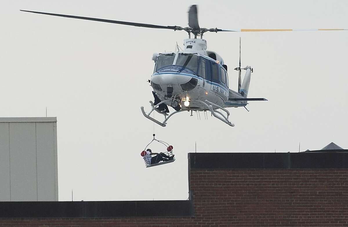 """TOPSHOTS A helicopter lifts a person off the roof as police respond to the report of a shooting at the Navy Yard in Washington, Dc on September 16, 2013. Departures have been halted at Washington's Reagan National Airport due to a shooting at the US Navy Yard, an official said Monday. Chris Paolino, a spokesman for the airport, said inbound aircraft are still landing and that the airport remains open to passengers. """"We can confirm that the FAA (Federal Aviation Administration) has halted aircraft departures from Reagan National due to an active law enforcement incident at the Washington Navy Yard,"""" Paolino told AFP via email. Several people have been wounded in the shooting at the nearby US Navy Yard in Washington, authorities said. The Navy said at least three shots were fired at 8:20 am (1320 GMT) in the headquarters building of the Naval Sea Systems Command. AFP PHOTO / Saul LOEBSAUL LOEB/AFP/Getty Images"""