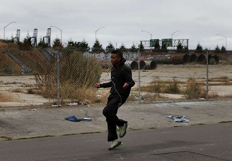 Devon Byers, 19, with Oakland's port as a backdrop, jumps rope on Pine Street for his morning workout. Photo: Lacy Atkins, The Chronicle
