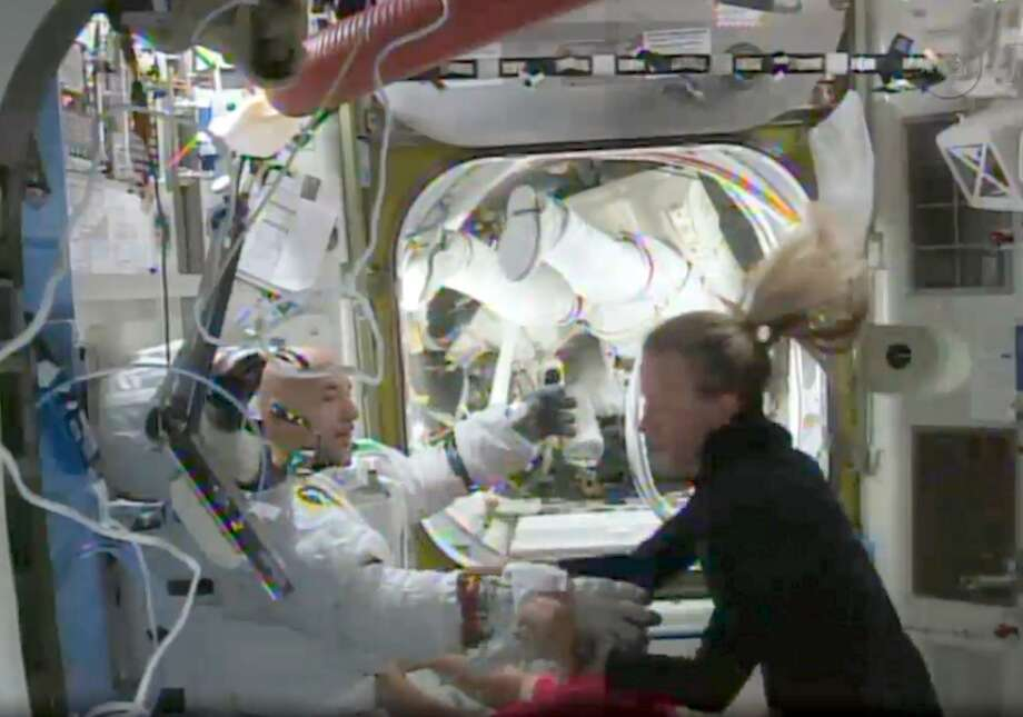 This July 16, 2013, NASA TV video image shows International Space Station(ISS) astronaut Karen Nyberg(R) assisting Italian astronaut Luca Parmitano after bringing him back into the station following an aborted space walk. Photo: HO, AFP/Getty Images