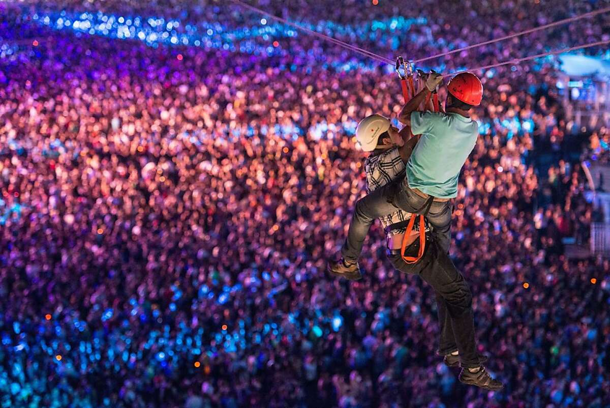 Can you wait until after his set? A rescuer comes to the aid of a man who stopped his pulley on a zip-line over the audience of a Justin Timberlake performance at the Rock in Rio music festival.