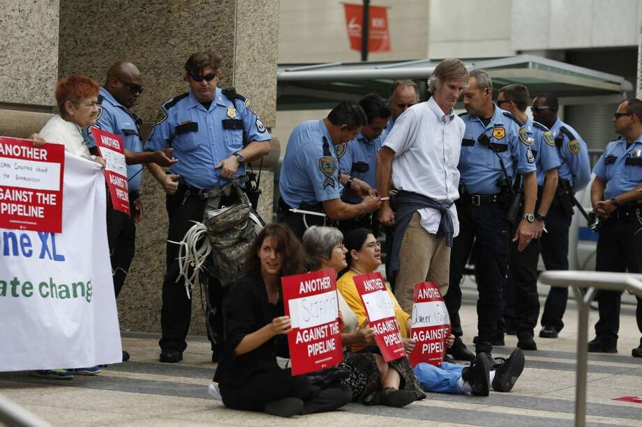 Protestors perform civil disobedience by chanting and holding signs while criminally trespassing Sept. 16, 2013 in Houston in front of the TransCanada headquarters in downtown.