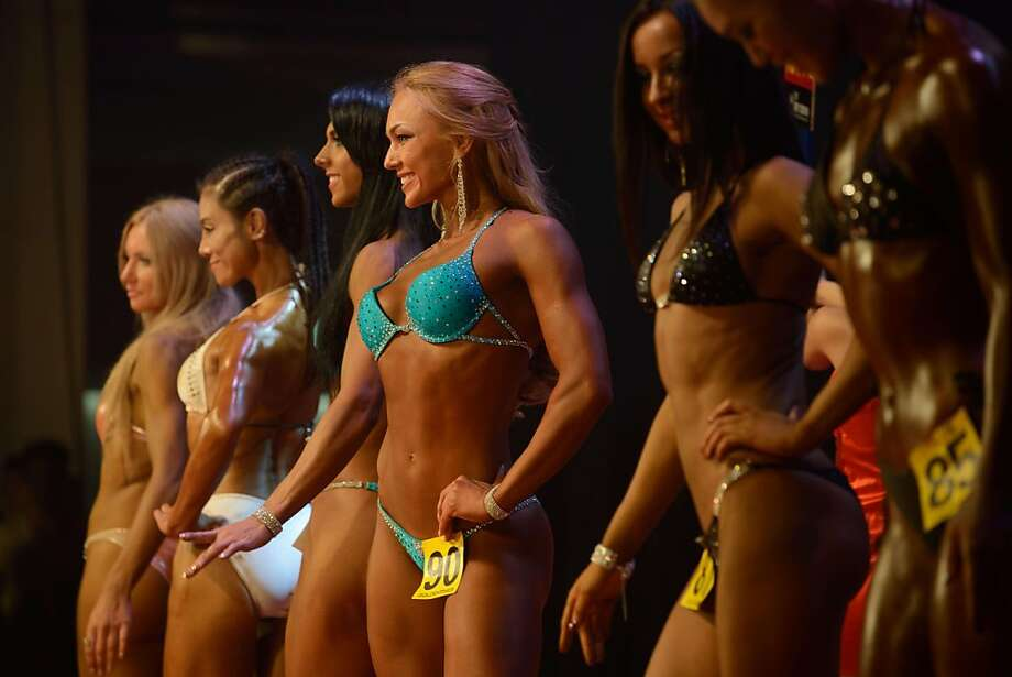 China embraces 'bikini fitness':Well-toned competitors flex and pose during a bodybuilding contest in Zhengzhou. More than 20   professionals, along with scores of amateurs, vied for a top prize of $13,000 in the Bodybuilding Grand   Prix. Photo: Ed Jones, AFP/Getty Images