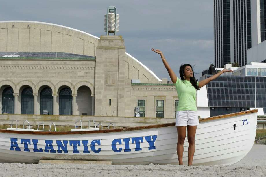 Miss America 2014 Nina Davuluri poses for photographers before engaging in the traditional dipping of the toes in the Atlantic Ocean the morning after being crowned Miss America, Monday, Sept. 16, 2013, in Atlantic City, N.J. Davuluri represented New York.  (AP Photo/Julio Cortez) ORG XMIT: NJJC104 Photo: Julio Cortez / AP