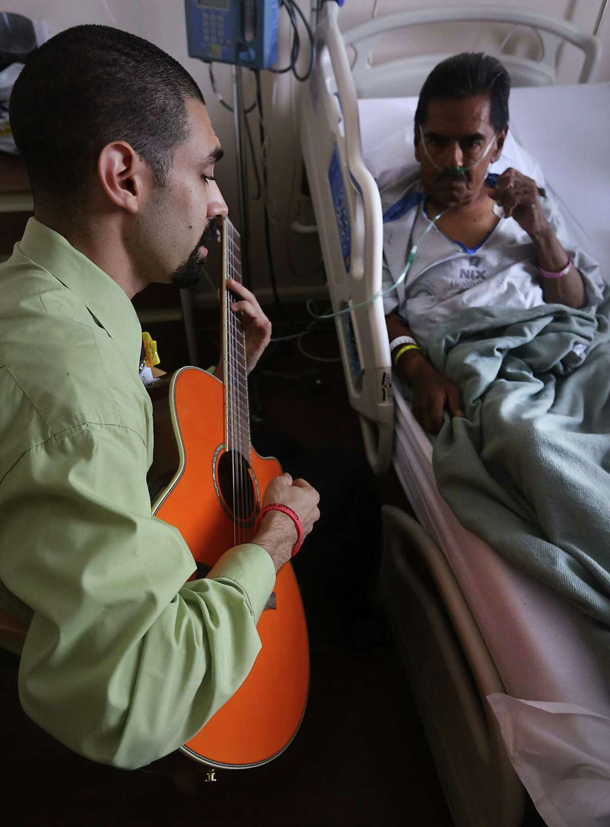 Raul Flores, right, plays his guitar for Manuel Perez at the Nix Health Center during a recent visit. Flores, an aspiring musical therapist, volunteers his time to play for patients at the downtown hospital.