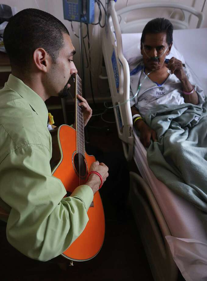 Raul Flores, right, plays his guitar for Manuel Perez at the Nix Health Center during a recent visit. Flores, an aspiring musical therapist, volunteers his time to play for patients at the downtown hospital. Photo: Photo By Bob Owen / San Antonio Express-News