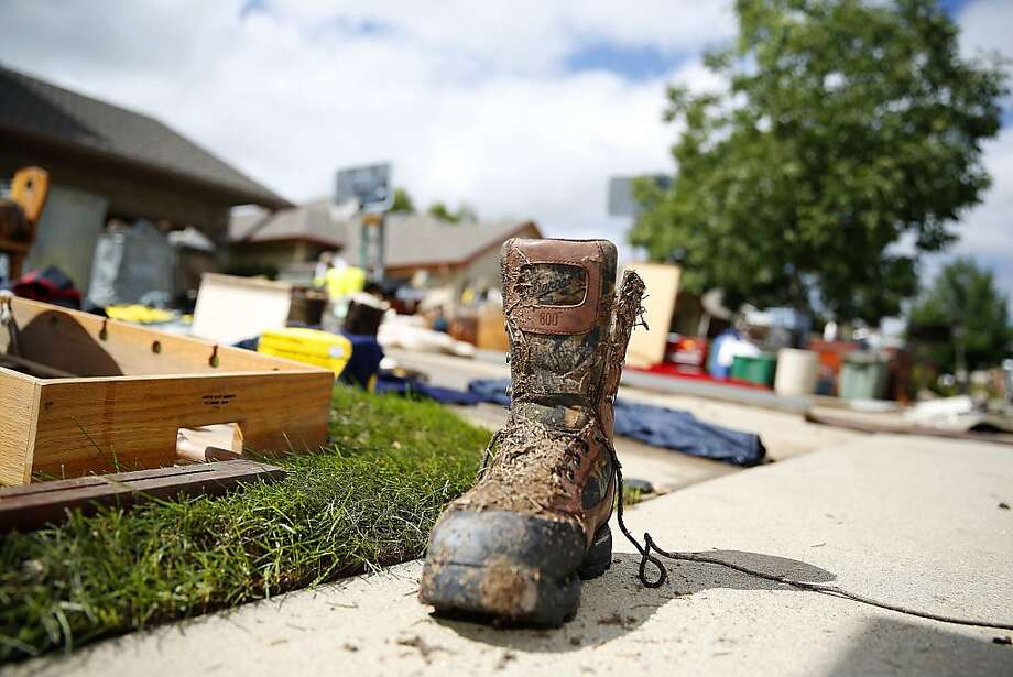 LONGMONT, CO - SEPTEMBER 16: A debris covered hunting boot sits in front of a home in Longmont, Colorado drying as residents clean up in in one of the hardest hit neighborhoods in the wake of a week of heavy flooding on September 16, 2013 in Longmont, Colorado. More than 600 people are unaccounted for and thousands were forced to evacuate after historic flooding devastated communities in Colorado. (Photo by Marc Piscotty/Getty Images) Photo: Marc Piscotty, Getty Images