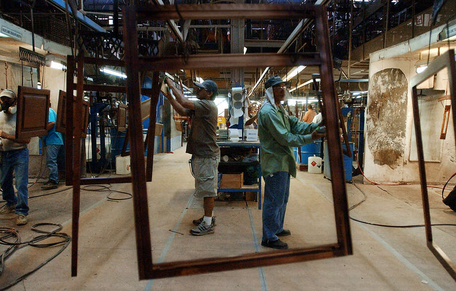 Cardell Cabinetry employees sand down pieces of cabinetry at the main manufacturing facility in this photo taken Sept. 30, 2003. The facility closed suddenly. Photo: Photo By Kin Man Hui / San Antonio Express-News