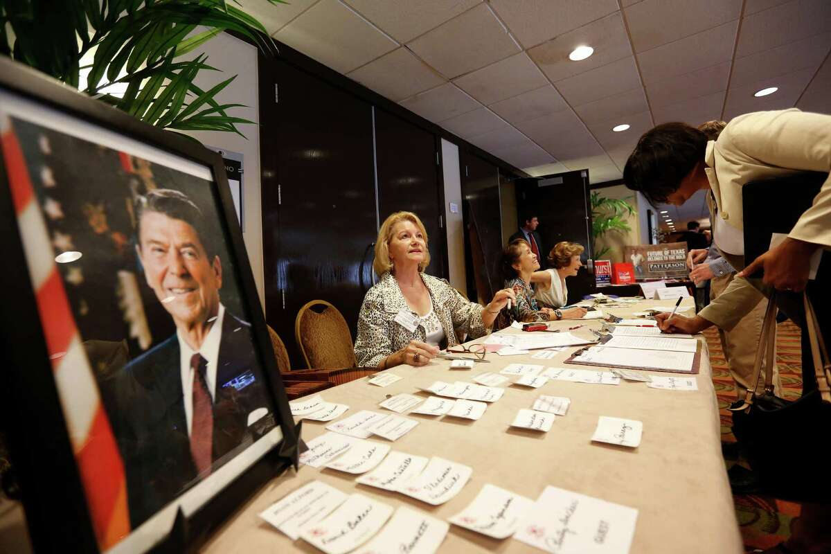 Patricia Henderson, center, helps check members in during a debate between the four candidates for lieutenant governor, Monday, September 16, 2013 at the Republican's women's forum at the Doubletree hotel in Houston, Texas.