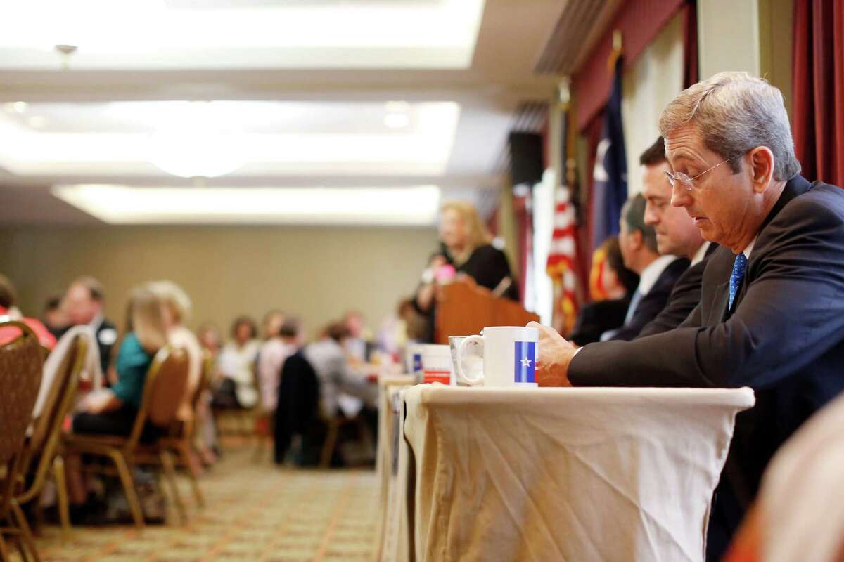 Candidate Jerry Patterson, right, takes notes during a debate between the four candidates for lieutenant governor, Monday, September 16, 2013 at the Republican's women's forum at the Doubletree hotel in Houston, Texas.