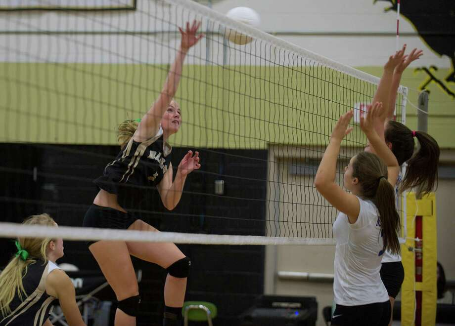 Joel Barlow's Hannah Goetz, 7, spikes the ball over Newtown's Mackenzie Lapp, 3, and Meghan Logan, 7, during a girls volleyball game at Joel Barlow High School in Redding, Conn, on Monday, September 16, 2013. Photo: H John Voorhees III