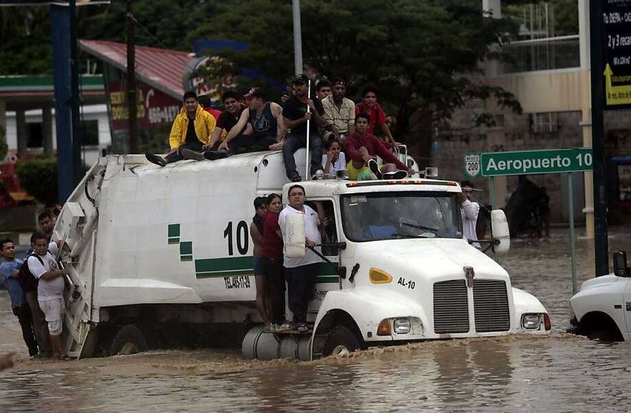 Residents attempt to leave the flooded area in Acapulco, hit by Tropical Storm Manuel. Photo: Pedro Pardo, AFP/Getty Images