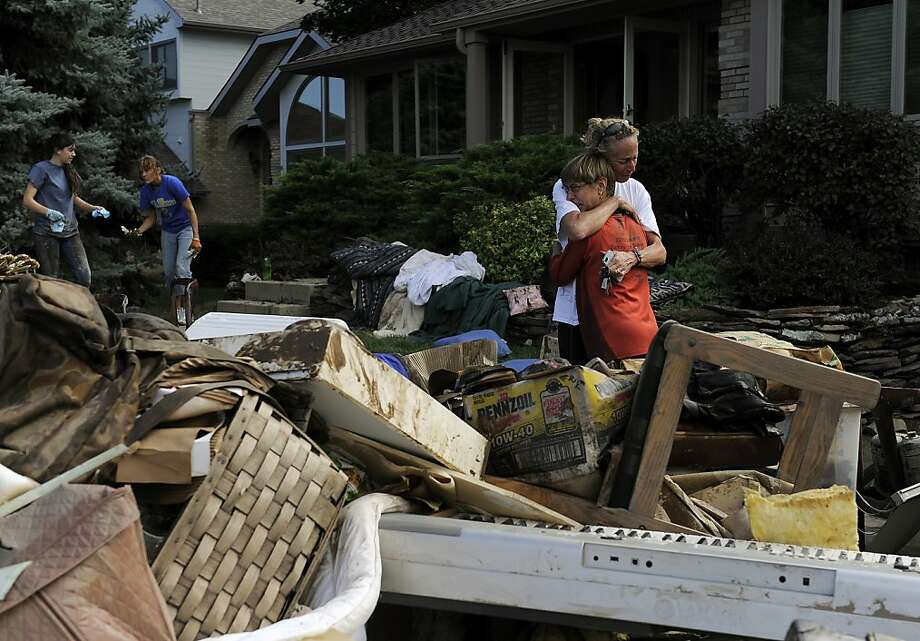Homeowner Chris Ringdahl, right, is comforted by family friend Hillari Hansen, left, in front of her possessions as they cleanup from the floodwaters in Longmont, Colo., on Monday, Sept. 16, 2013. Floodwaters have affected a 4,500 square-mile section of the state inundating entire neighborhoods and destroying bridges and roads. (AP Photo/Chris Schneider) Photo: Chris Schneider, Associated Press