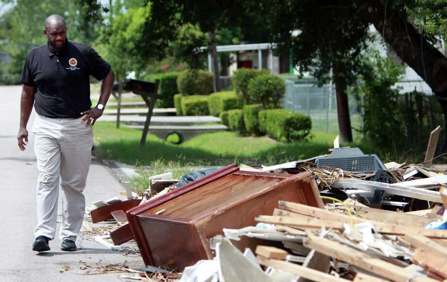 Councilman Jerry Davis walks in front of an empty lot in the 800 block of Miley where illegal dumping is occurring. Photo: Mayra Beltran, Staff / © 2013 Houston Chronicle