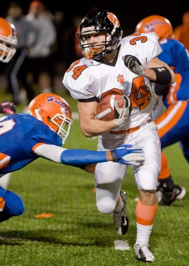Ridgefield High School's Will Bonaparte slips through a tackle during a game against Danbury High School, played at Danbury. Wednesday, Nov. 21, 2012 Photo: Scott Mullin
