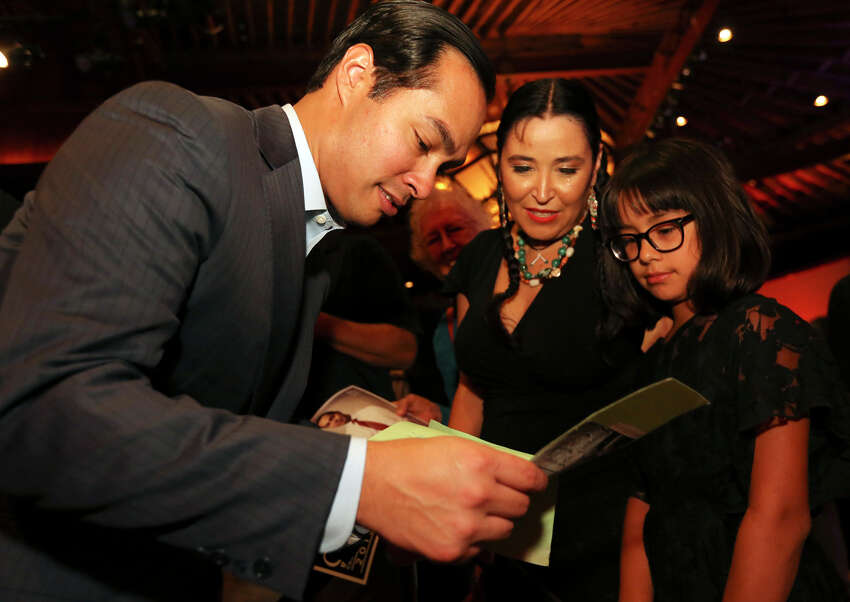 Mayor Julián Castro (left) looks at a handmade gift from Marisela Barrera and her daughter Valentina Barrera-Ibarra, 9, during the twins' 39th birthday celebration held Monday Sept. 16, 2013 at the Pearl Stable.