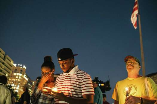 Brittany Carter, of Bowie, Md., left, Jibri Johnson, of Landon, Md., and Bryan Beard, of Washington, D.C., hold candles in remembrance of people affected by gun violence during a vigil at Freedom Plaza in Washington, D.C., Monday night. The vigil, during which organizers called for stricter gun laws, was in remembrance of the 12 victims killed in a shooting at the Washington Navy Yard earlier in the day. Photo: Greg Kahn, Getty Images / 2013 Getty Images